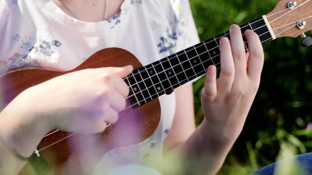ung vacker flicka spela ukulele gitarr - akustisk gitarr bildbanksvideor och videomaterial från bakom kulisserna