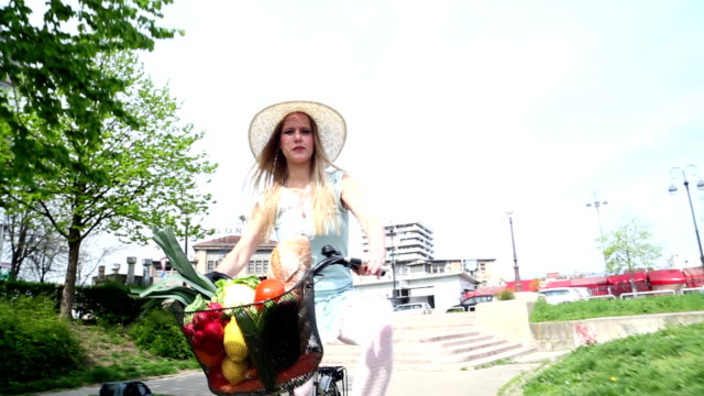 Young beautiful girl riding bike video