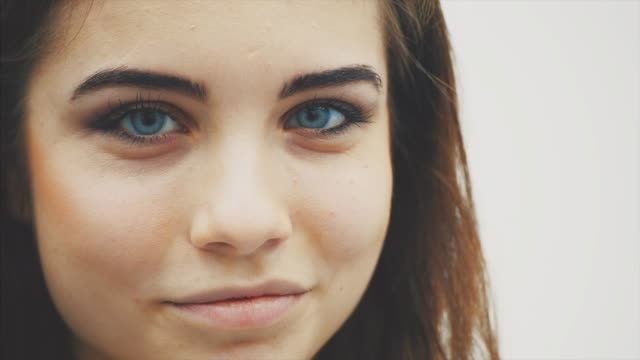 vídeos de stock e filmes b-roll de young beautiful girl standing in profile the looking at the camera with curious face expression, raising her eyebrow, winking at the camera and smiling. - sobrancelha