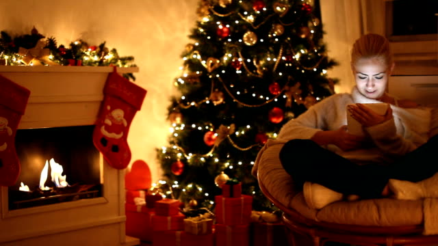 Young beautiful girl using digital tablet on Christmas night Young beautiful girl enjoying on the Christmas Eve she use a digital tablet in front of a fireplace near a Christmas tree christmas stocking stock videos & royalty-free footage