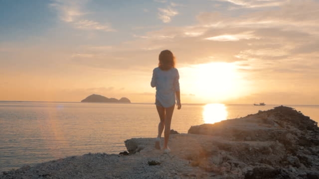 young beautiful girl walking on a sea shore to sunset, Over the shoulder shot video