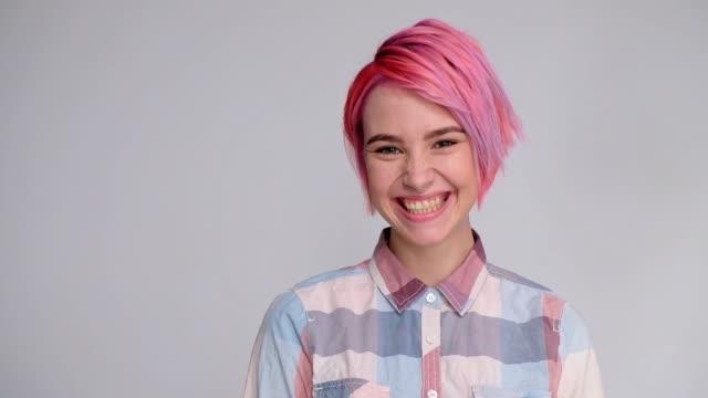 vídeos y material grabado en eventos de stock de joven hermosa chica con un pelo corto cortado pixie bob. coloración del cabello color rojo, color rosa. camisa en una bodega, estilo casual. - cabello corto