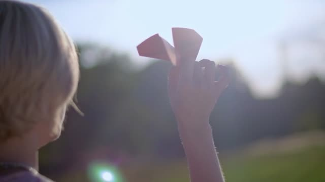 A young, beautiful girl with a tattoo on her hand launches a paper airplane.