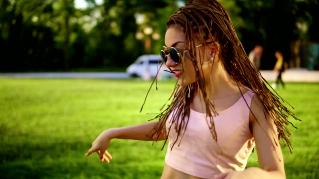Young beautiful girl with dreads dancing in a park. Beautiful woman in jeans and sunglasses listening to music and dancing during a sunny day. Slowmotion shot. Young beautiful girl with dreads dancing in a park. Beautiful woman in jeans and sunglasses listening to music and dancing during a sunny day. Slowmotion shot. locs hairstyle stock videos & royalty-free footage