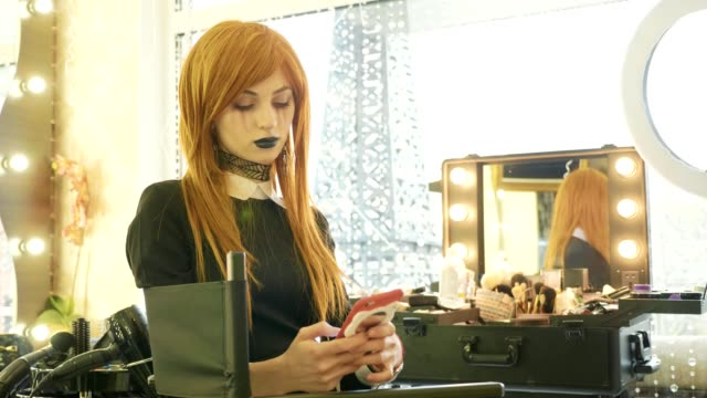 Young beautiful girl with halloween makeup using smart phone at beauty salon video