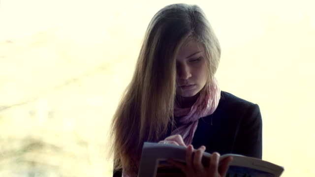 Young, beautiful girl writing in a notebook - Stock video video