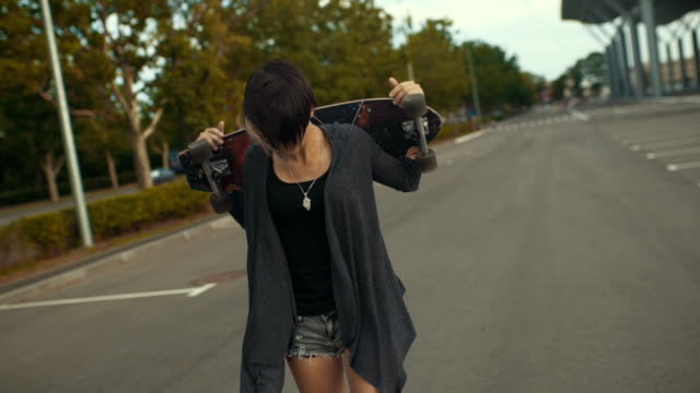 年輕漂亮時髦的女人走在街上,經營手滑板或退潮 - {{asset.href}} 個影片檔及 b 捲影像