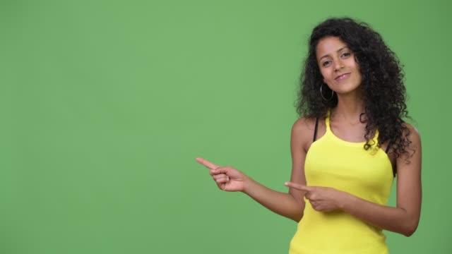 若い美しいヒスパニック系女性何かを示す - 指差す 女性点の映像素材/bロール