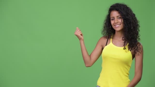 Young beautiful Hispanic woman showing something Studio shot of young beautiful Hispanic woman with curly hair against chroma key with green background snapping stock videos & royalty-free footage