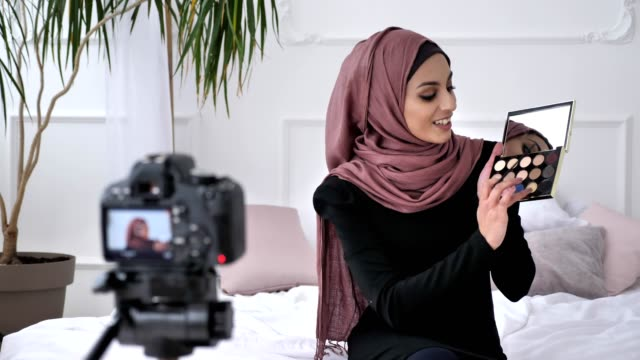 Young beautiful indian girl in hijab blogger talking on camera, smiling, showing a new purchase, cosmetics, Eyeshadow Pallet, home comfort in the background. 60 fps video