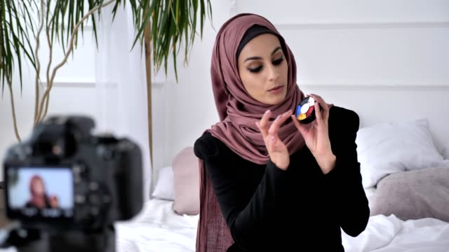 Young beautiful indian girl in hijab blogger talking on camera, smiling, showing a new purchase, cosmetics, aquagrum, home comfort in the background. 60 fps video