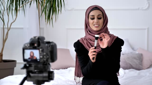 Young beautiful indian girl in hijab blogger talking on camera, smiling, talking at the camera, showing a new purchase, makeup brush, make-up concept, home comfort in the background. 60 fps video