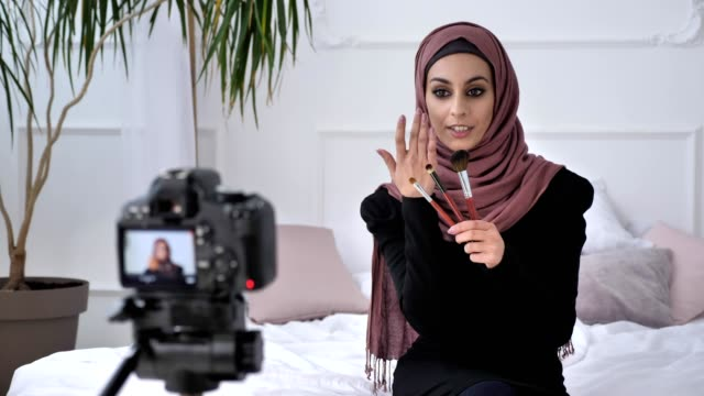 Young beautiful indian girl in hijab blogger talking on camera, smiling, talking at the camera, showing a new purchase, three makeup brushs, make-up concept, home comfort in the background. 60 fps video