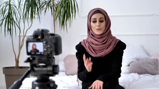 Young beautiful indian girl in hijab blogger talking on camera, counts, outraged, gesturing, white room, home comfort in background. Close up 50 fps video