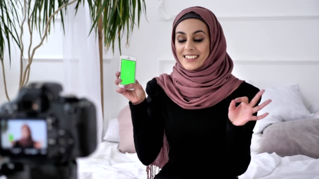 Young beautiful Indian girl in hijab recommends an application on a smartphone, smiling, talking at the camera, chroma key, green screen concept. 50 fps video
