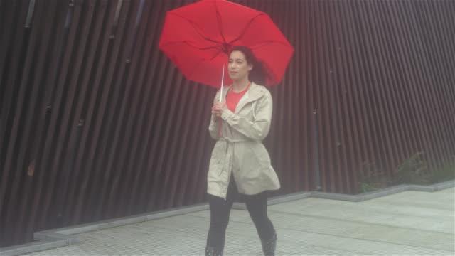 vídeos de stock e filmes b-roll de young beautiful latin woman walking with an umbrella on a rainy day. the wind bends the umbrella inside out - guarda chuva