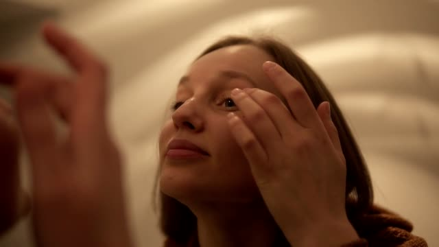 Young beautiful light brown haired girl is applying wrinkle cream on eyelid looking in the mirror. Handheld footage video