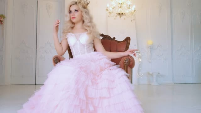 Young beautiful moody princess bored in medieval armchair. White room in style barroco. Vintage crystal chandelier. Woman blond loose curly hair. Golden royal crown. Long luxury elegant pink ball gown