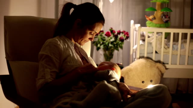 vídeos de stock e filmes b-roll de young beautiful mother, breastfeeding her newborn baby boy at night, dim light. mom breastfeeding infant - amamentação