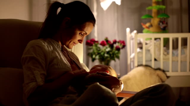 vídeos de stock e filmes b-roll de young beautiful mother, breastfeeding her newborn baby boy at night, dim light. mom breastfeeding infant. - amamentação