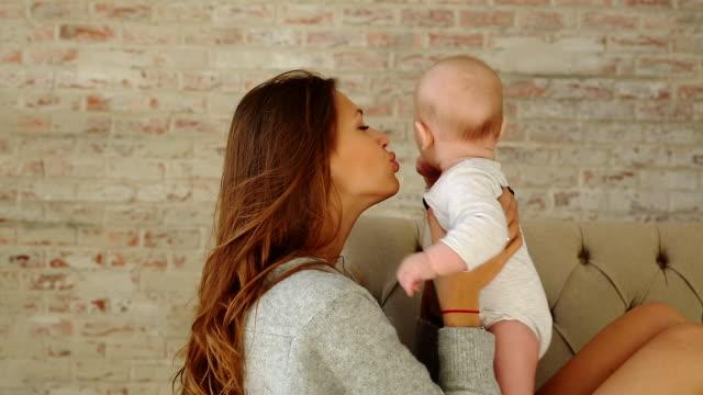 young beautiful mother plays with her infant baby and kisses it on the sofa - brązowe włosy filmów i materiałów b-roll