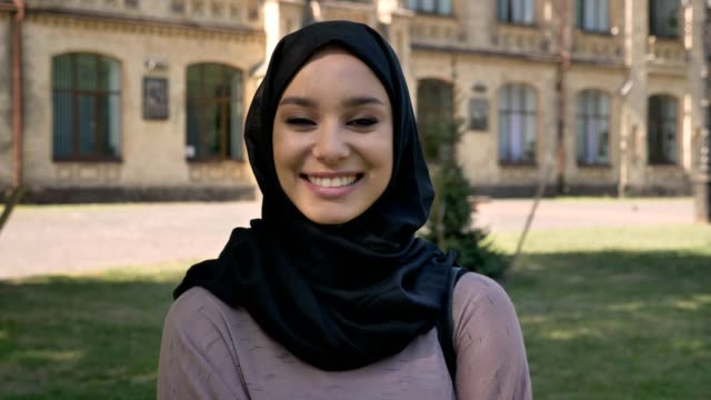 young beautiful muslim girl in hijab is smiling and giggling in daytime in summer, watching at camera, building on background, religiuos concept - islam filmów i materiałów b-roll