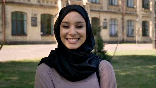 vídeos y material grabado en eventos de stock de joven hermosa chica musulmana en hijab es sonreír y reír durante el día en verano, mirando a cámara, basándose en antecedentes, concepto de epoca - islam