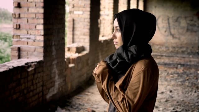 Young beautiful muslim woman in black hijab standing in abandoned building and looking at camera with scared and terrified expression video