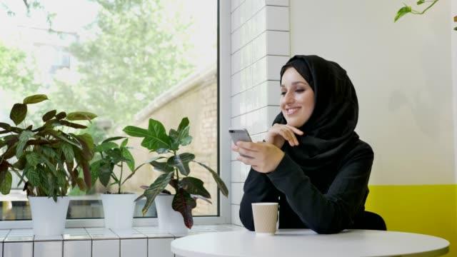 unga vackra muslimsk kvinna i hijab håller telefonen och ler, sitter i café, glada - anständig klädsel bildbanksvideor och videomaterial från bakom kulisserna