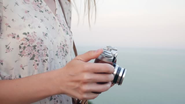 young beautiful photographer woman stands in field with vintage camera on sea background. preparing to take a photo on a retro camera. - figura femminile video stock e b–roll