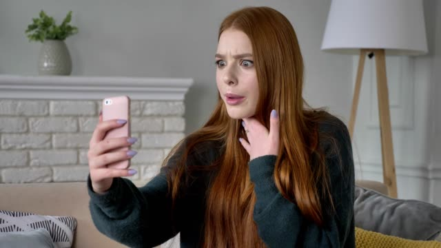 Young beautiful red-haired teen girl uses a smartphone, video chat, home comfort in the background. 60 fps video