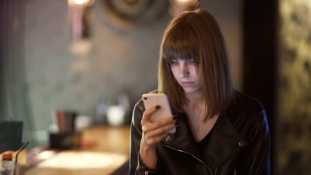 年輕漂亮的紅頭髮的女人坐在咖啡館或酒吧, 並使用智慧手機 - {{asset.href}} 個影片檔及 b 捲影像