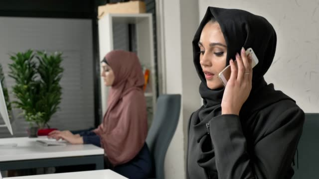 Young beautiful sad girl in black hijab sits in the office and speaks on the smartphone. Unhappy 60 fps video
