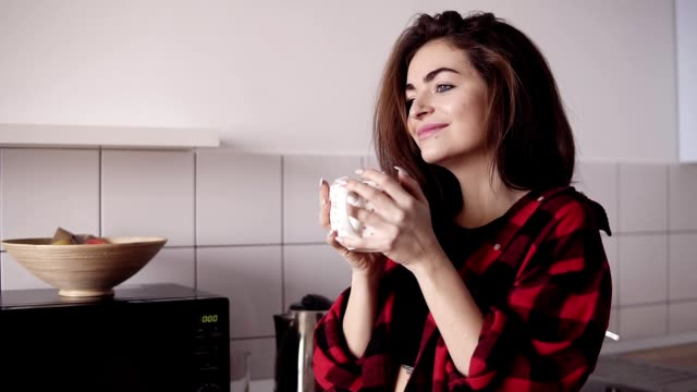 Young beautiful sexy girl in flannel shirt drinking tea and dreaming about something while standing in a cozy loft kitchen. video