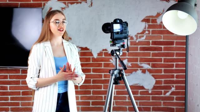 vídeos de stock e filmes b-roll de young beautiful smiling female blogger shooting video blog using camera at production studio - weatherman