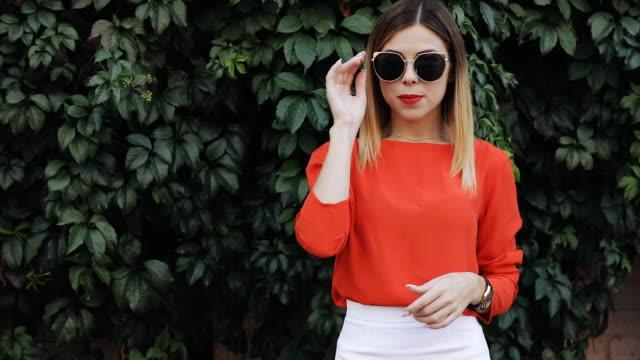Belle jeune femme souriante dans lunettes de soleil près de la paroi en bois croisé ses bras - Vidéo