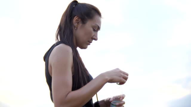vídeos de stock e filmes b-roll de young beautiful sportswoman drinks water from a bottle outdoors after training - climate clock