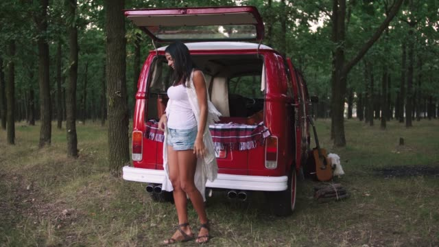 young beautiful stylish woman dancing near hippie retro bus in forest and having some fun, slow motion - hippie fashion stock videos & royalty-free footage