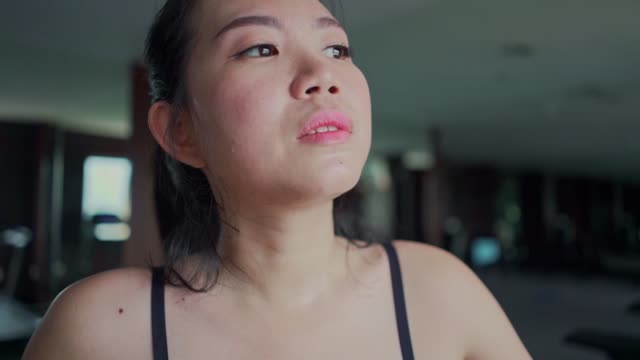 young beautiful sweaty and tired asian korean runner woman cooling off breathing exhausted on gym treadmill after hard jogging workout - irriducibilità video stock e b–roll