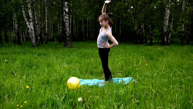 Young beautiful teenager girl practicing fitness exercising outdoors, in park in summer day. HD shooting static camera video