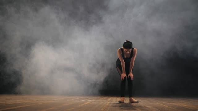 黒いスーツの若い美しい疲れバレリーナはパフォーマンス後煙で舞台に立ちます。息のバレエ ダンサーの女、息がかかります。スローモーション - バレリーナ点の映像素材/bロール