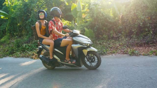 young beautiful tourist couple rides the jungle on a scooter wearing helmets. travel, freedom, happiness, vacation, honeymoon concept. - bali filmów i materiałów b-roll