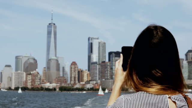 Young beautiful tourist girl taking photos of Manhattan in New York, America on smartphone from the boat on East river video