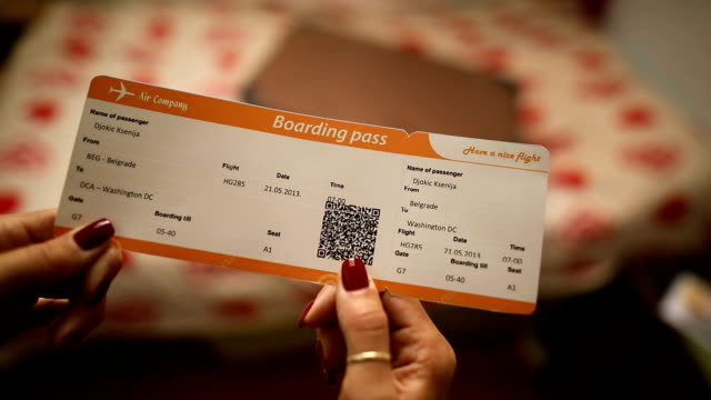 Young beautiful tourist woman holding boarding pass ticket close up
