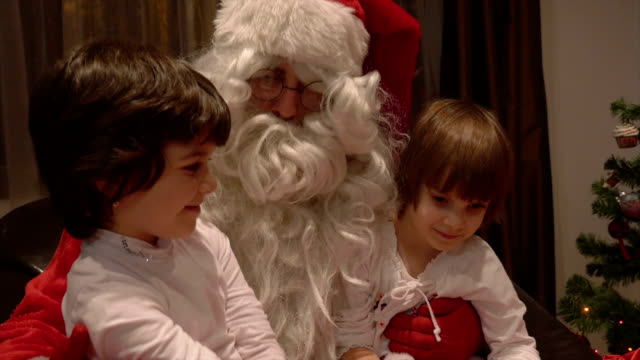 Young beautiful twin girls sitting in Santa Claus lap on Christmas day video