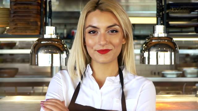 giovane bella cameriera in grembiule in piedi con le braccia incrociate in bar o ristorante - mestiere nella ristorazione video stock e b–roll