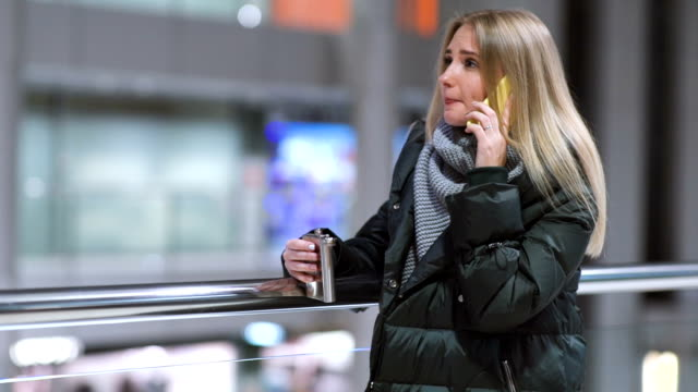 young beautiful woman alone drinks whiskey alcohol from flask and talking on phone in shopping mall video