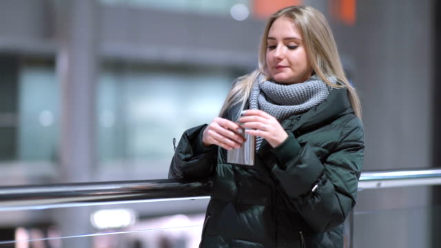 young beautiful woman alone drinks whiskey alcohol from flask in shopping mall video