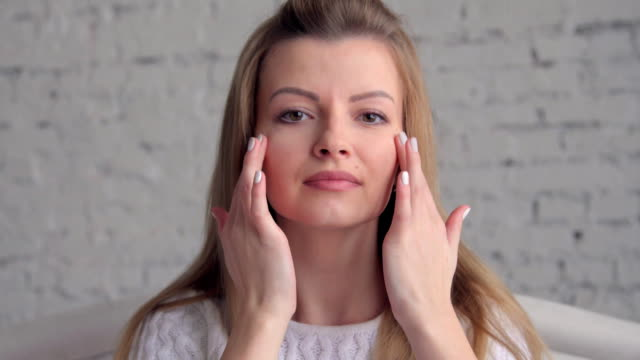 Young beautiful woman applying cream on her face video