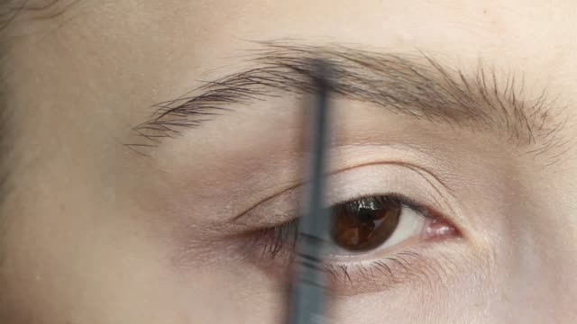 stockvideo's en b-roll-footage met jonge mooie vrouw het aanbrengen van wenkbrauwpotlood close-up. schoonheid, make-up concept - eyeliner